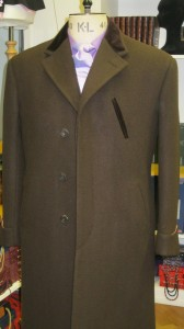 Single breasted overcoat. Fly front with slanted glove pocket.